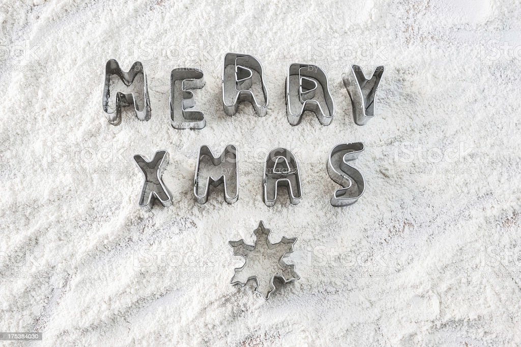Merry Christmas and snowflake cookie cutters on flour stock photo
