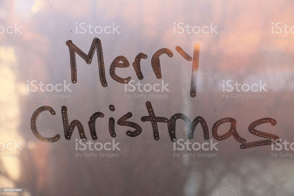 Merry Christmas text written on the glass stock photo