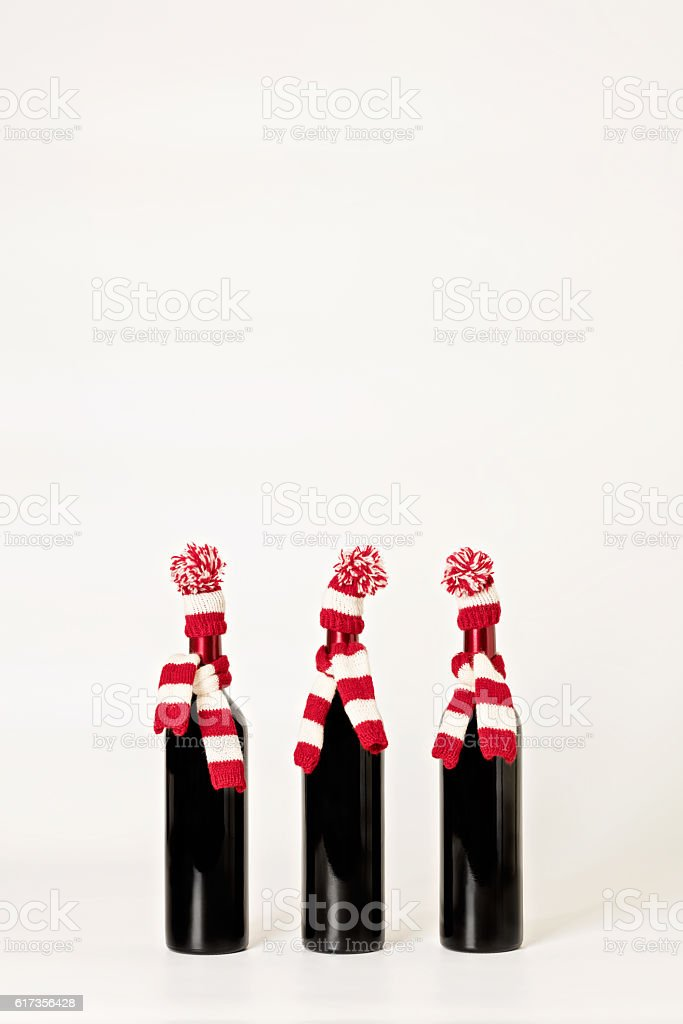 Merry Christmas. Three bottles  wine in knitted caps and scarfs stock photo