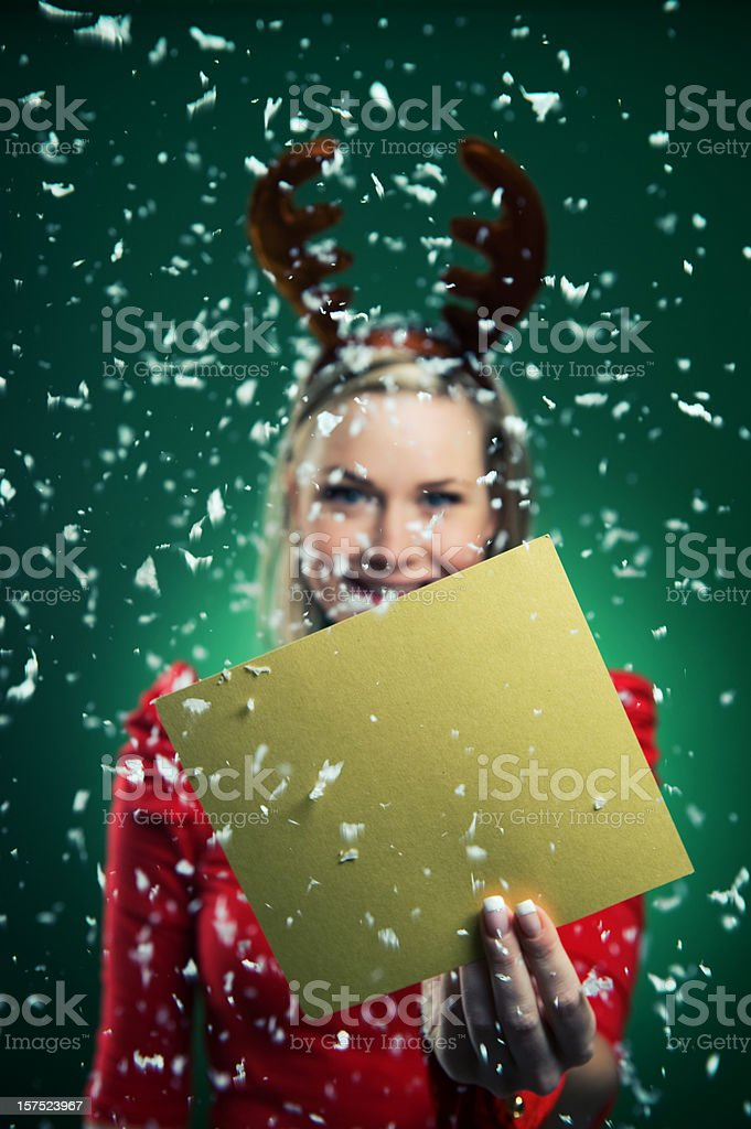 Merry Christmas - woman in reindeer costume holding sign royalty-free stock photo