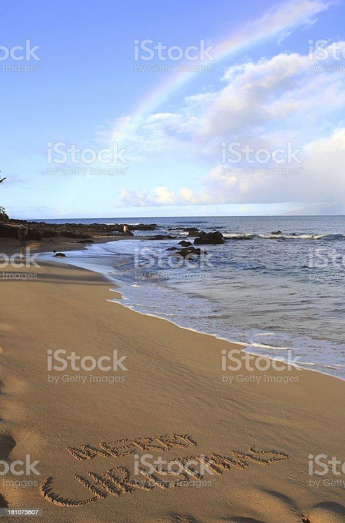 Merry Christmas written on Maui Hawaii beach sand and rainbow royalty-free stock photo