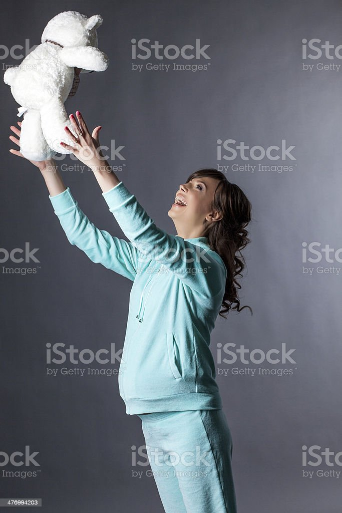 Merry expectant mother plays with teddy bear royalty-free stock photo