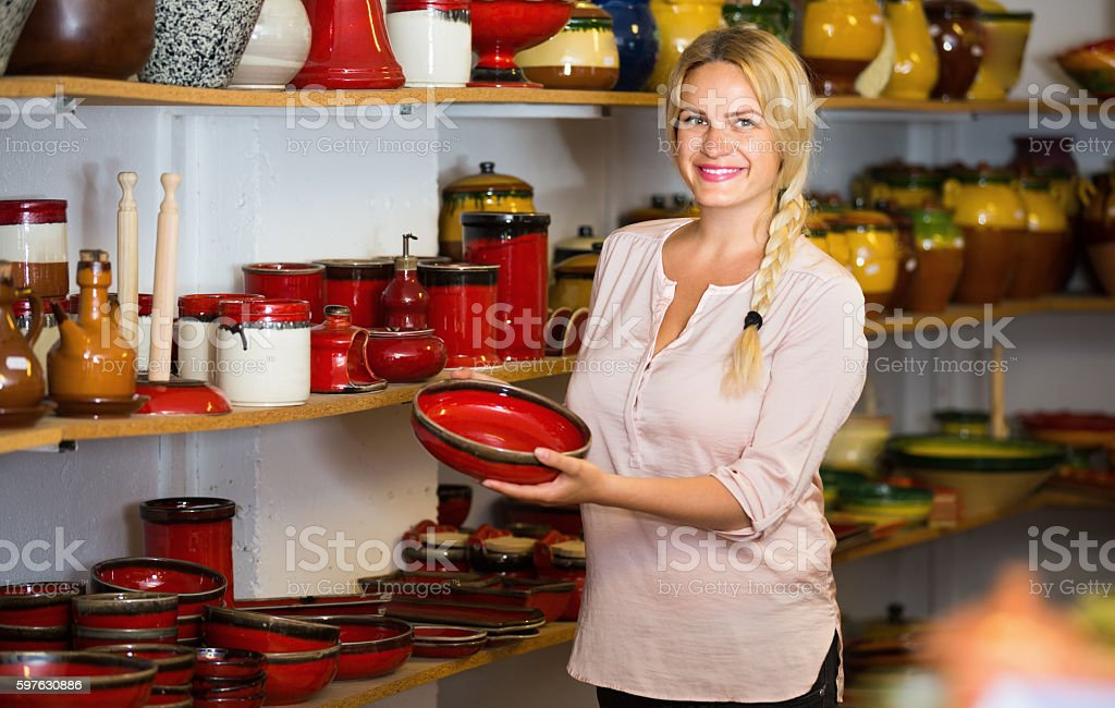 merry female customer picking red glazed crockery stock photo