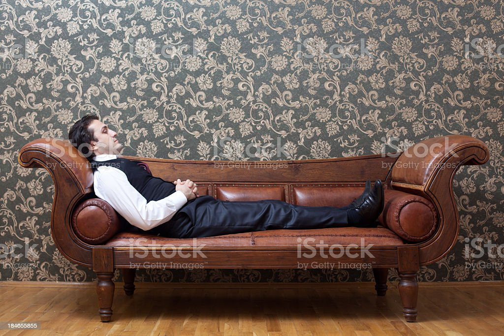 Mesmerized man lying down on coach in psychiatrist office stock photo