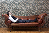 Mesmerized man lying down on coach in psychiatrist office