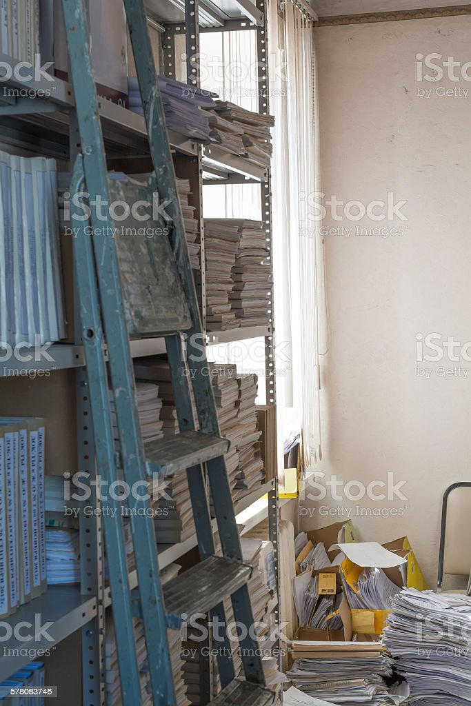 Mess in the archive. Old folding ladder. stock photo