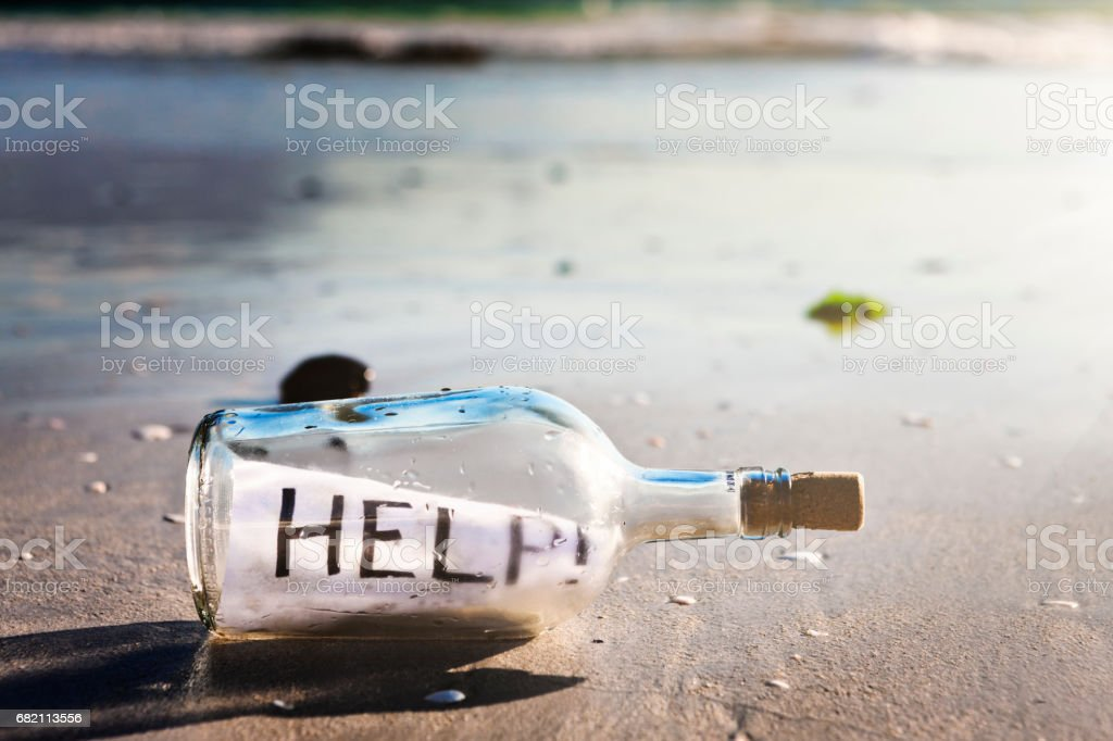 Message in a bottle on beach reads 'HELP!' stock photo