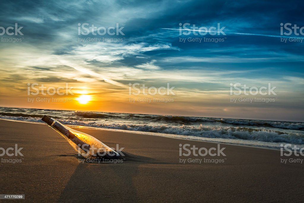Message in a bottle on sea shore stock photo