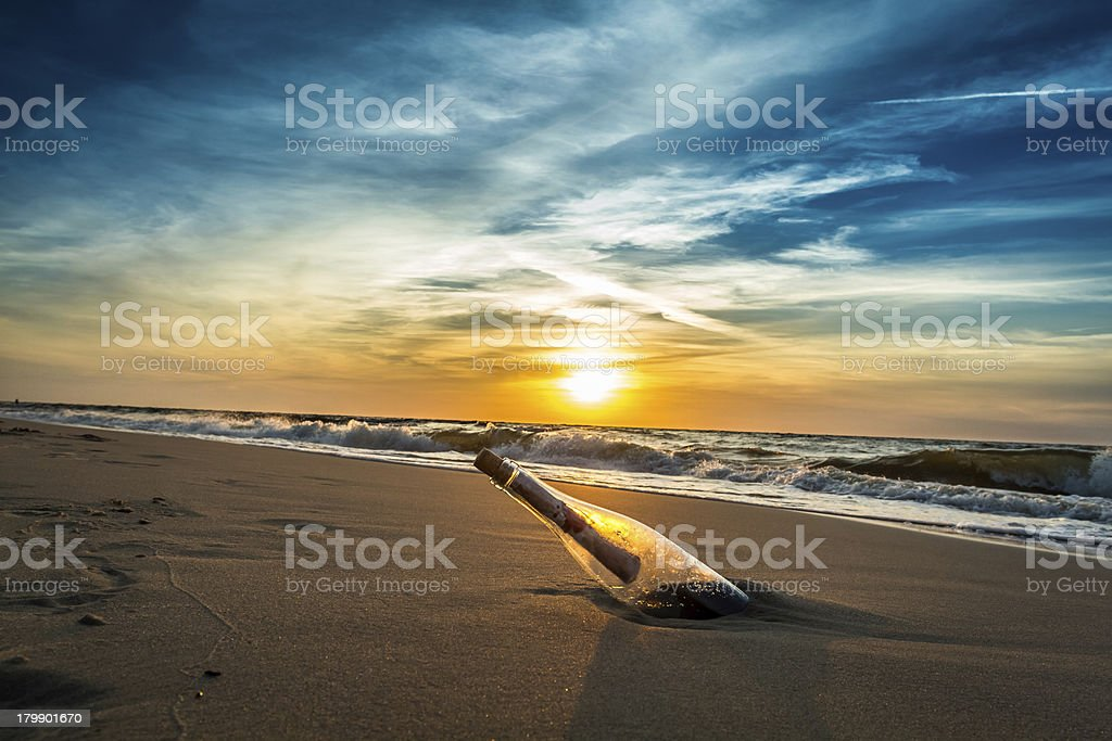 SOS message in a bottle on the beach stock photo
