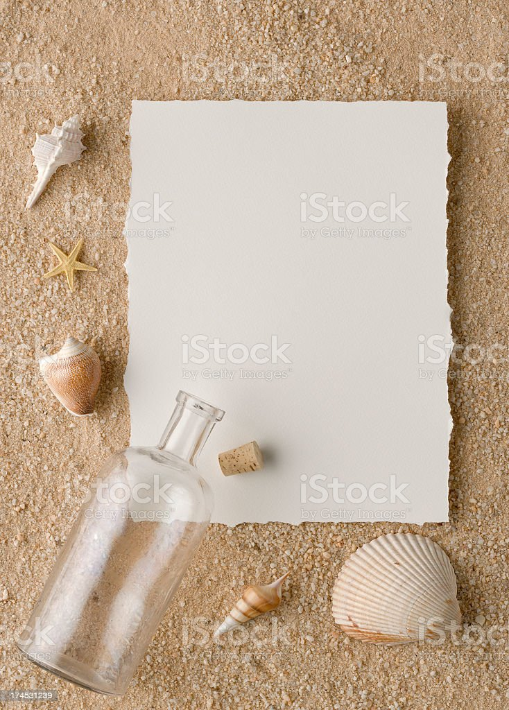 Message in a Bottle. Paper and Seashells on Sandy Beach. royalty-free stock photo