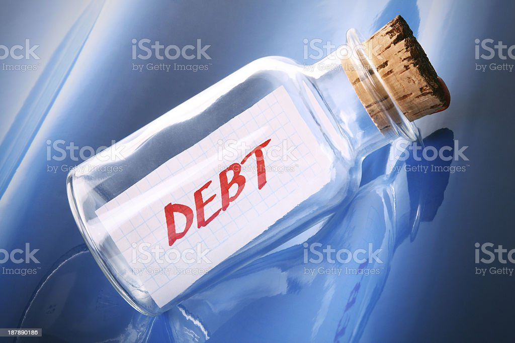 Message in a bottle saying 'debt'. Money concept. stock photo