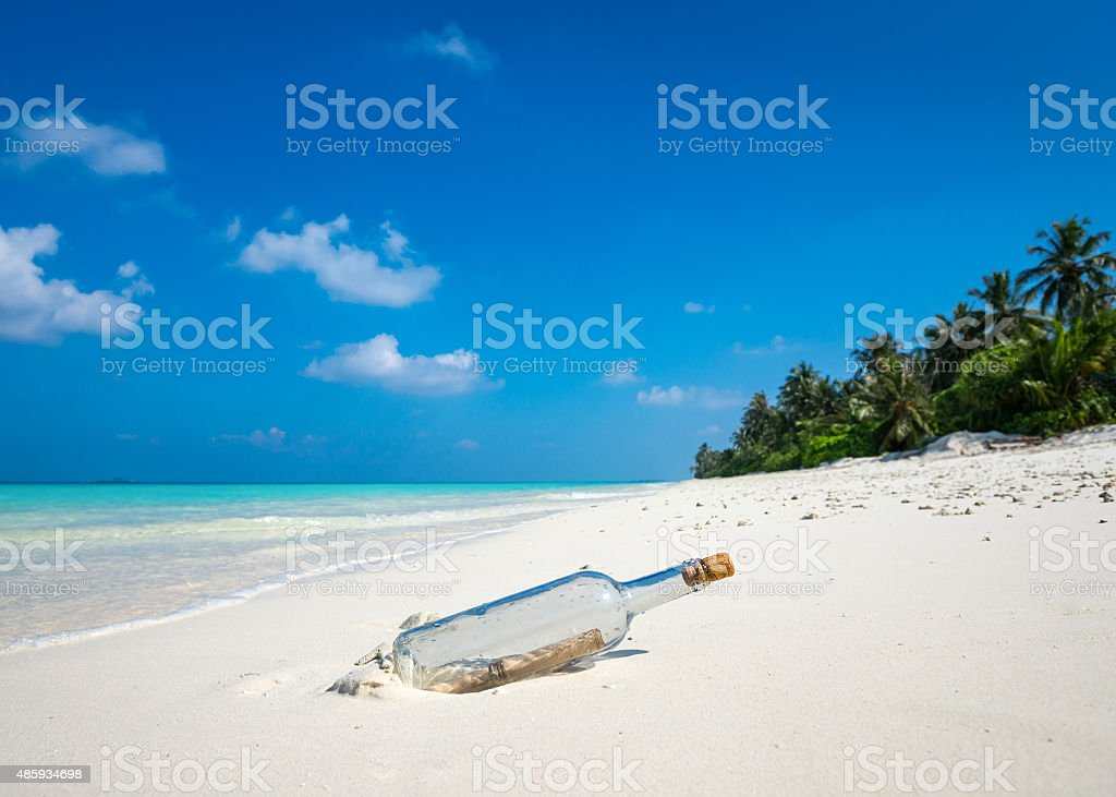 Message in a bottle washed ashore on a tropical beach. stock photo
