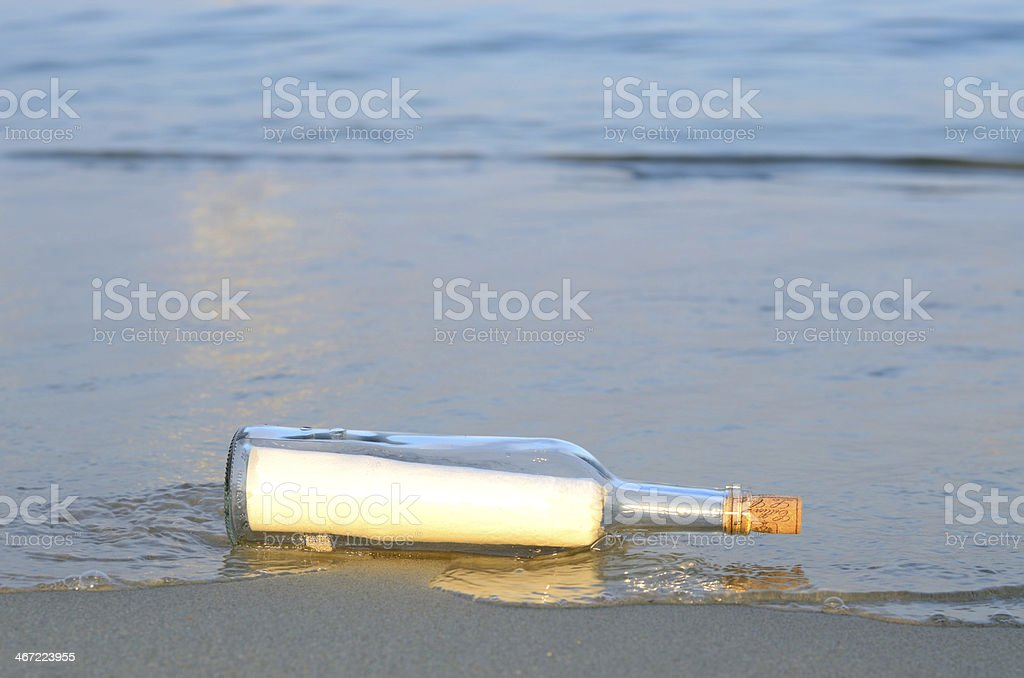 Message in a bottle washed on the beach stock photo