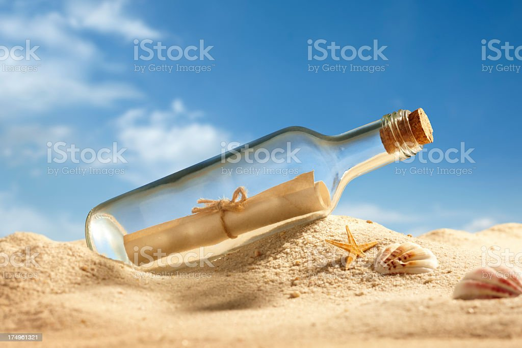Message in a glass bottle on sand next to shells stock photo