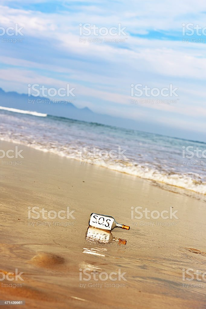SOS message in bottle lies ignored on empty deserted beach stock photo