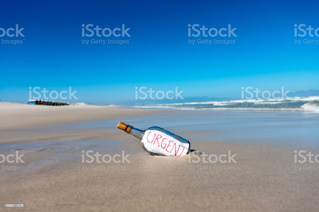 Message in bottle on deserted beach says Urgent stock photo