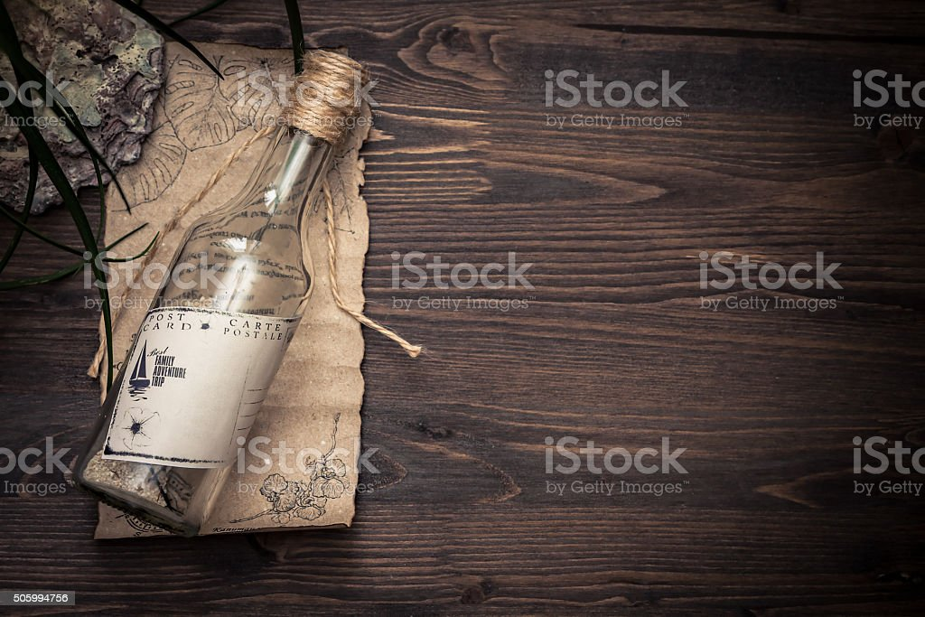 Message in bottle with copy space on tropical  wooden background stock photo