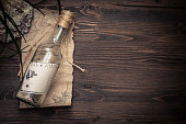 Message in bottle with copy space on tropical  wooden background