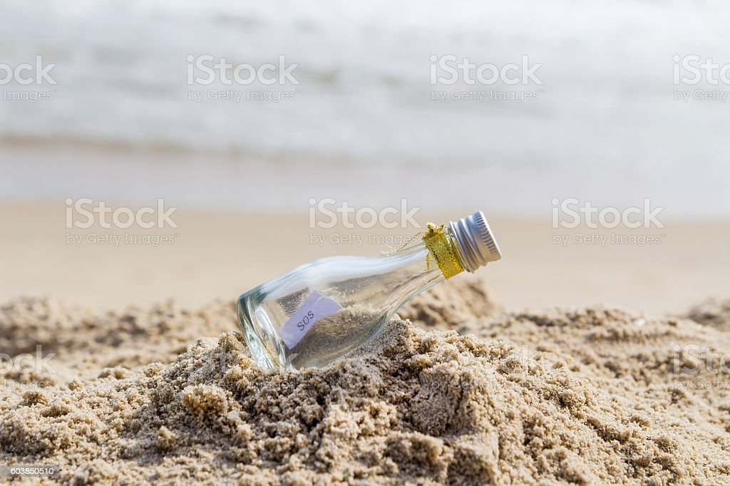 SOS message in glass bottle on the beach. stock photo