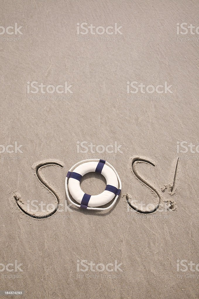 SOS Message in the Sand with Lifesaver stock photo