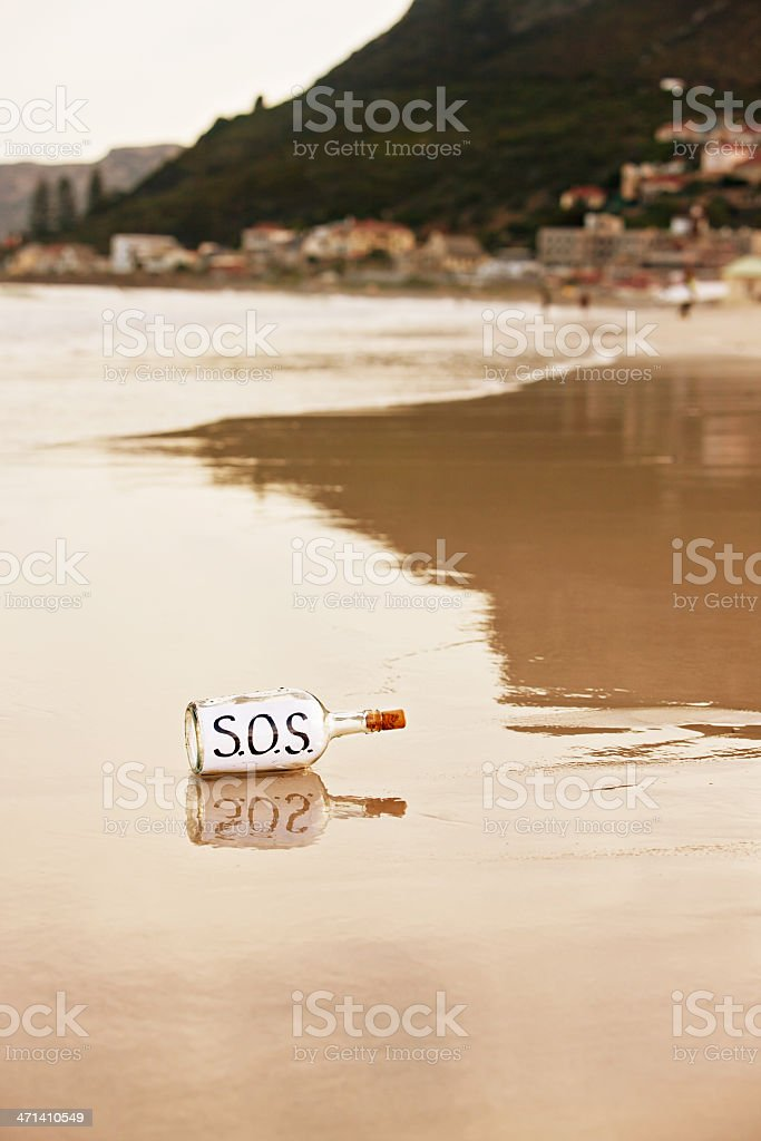 Message in washed-up bottle says SOS - help urgently required stock photo