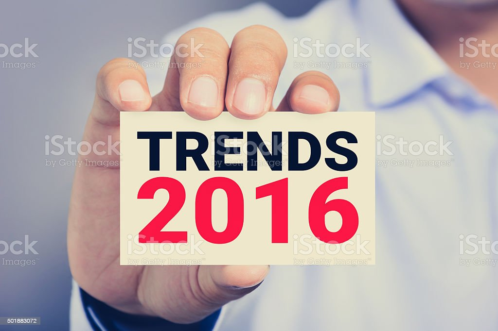 TRENDS 2016, message on business card held by a man stock photo