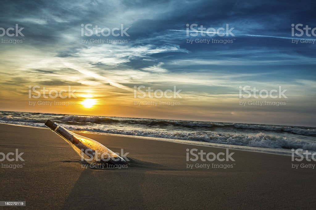 Message with letter inside the bottle on a beach stock photo