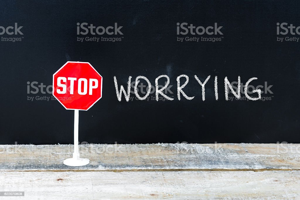 STOP WORRYING message written on chalkboard stock photo