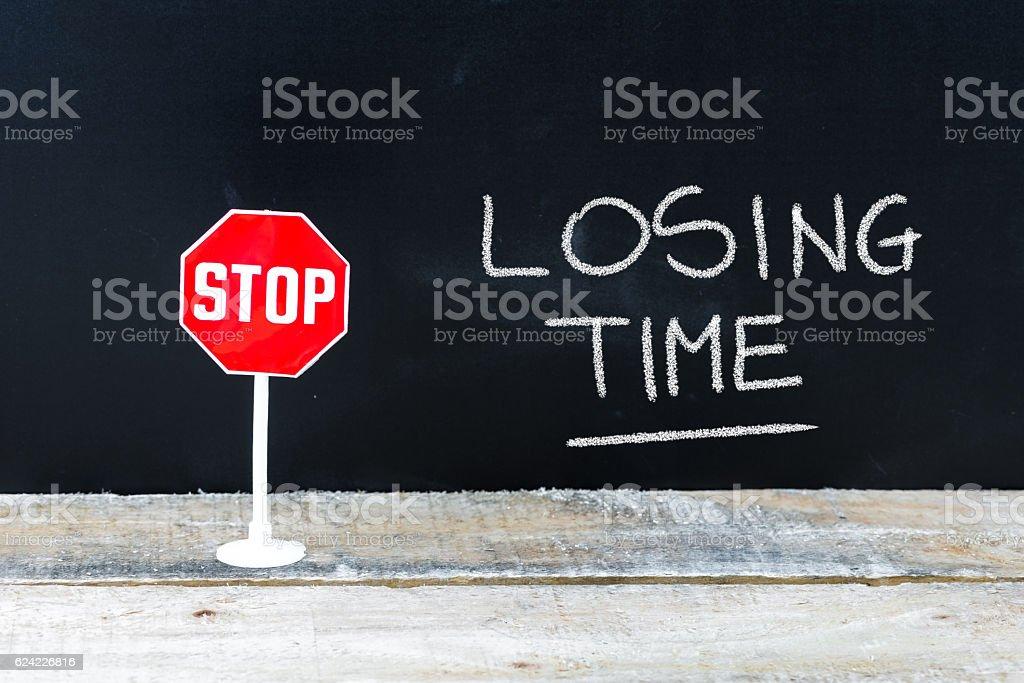 STOP LOSING TIME message written on chalkboard stock photo