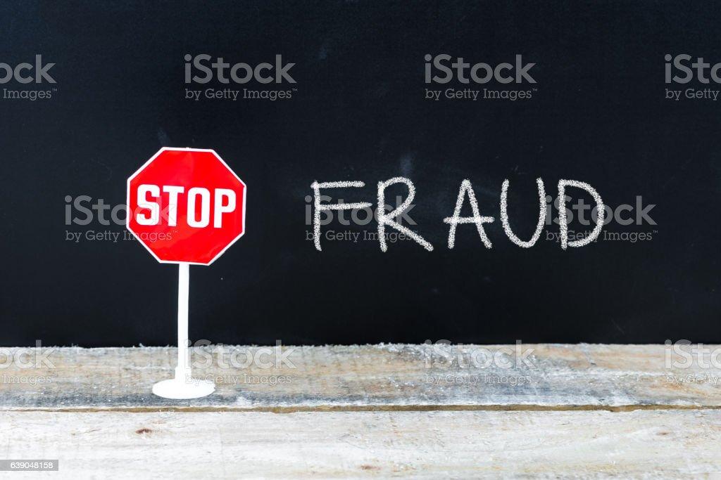 STOP FRAUD message written on chalkboard stock photo