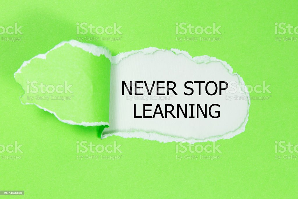 NEVER STOP LEARNING message written under torn paper. stock photo