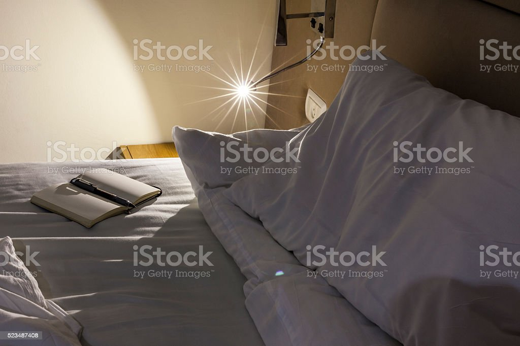Messed bed with reading light notebook pen glass of water stock photo