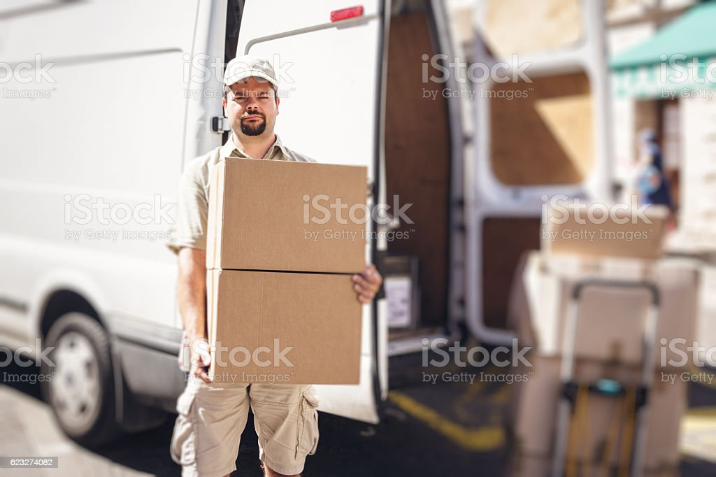Messenger delivering parcel, standing next to his van stock photo
