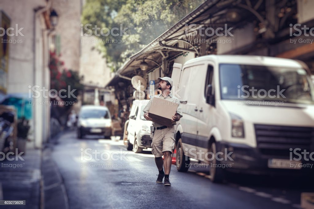 Messenger delivering parcel, walking in street next to his van stock photo