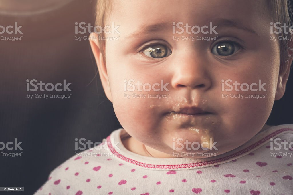 Messy baby girl portrait after lunch stock photo