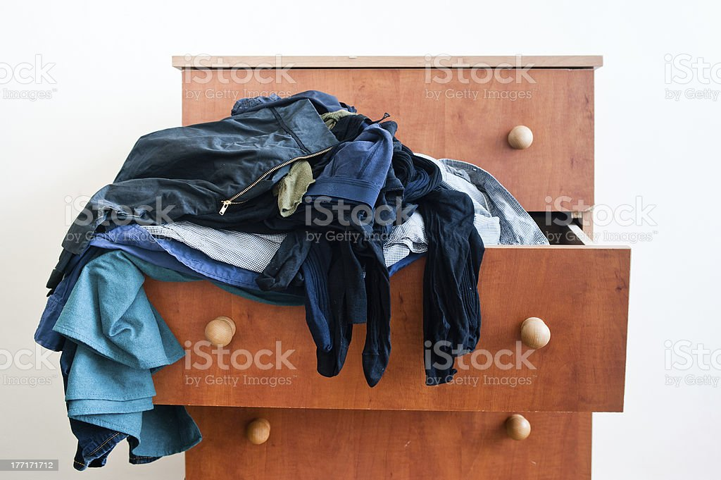 Messy chest of drawers with clothes stock photo