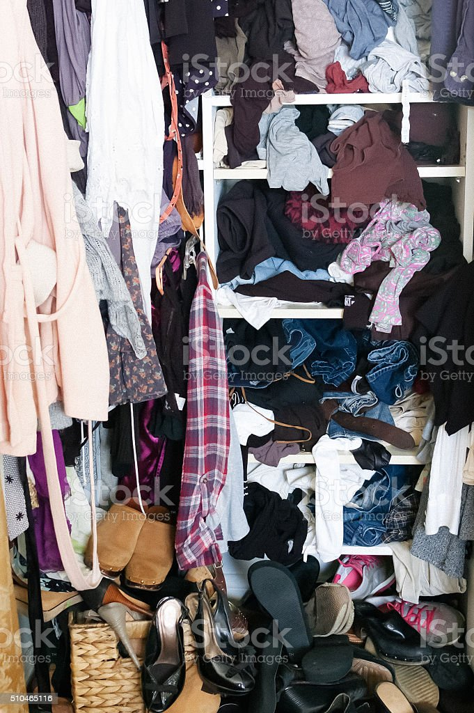 Messy woman's closet full of clothes and shoes stock photo