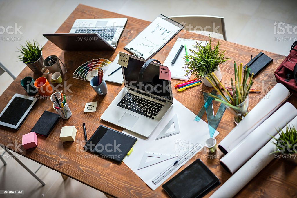 Messy desk of young startup coworking business stock photo