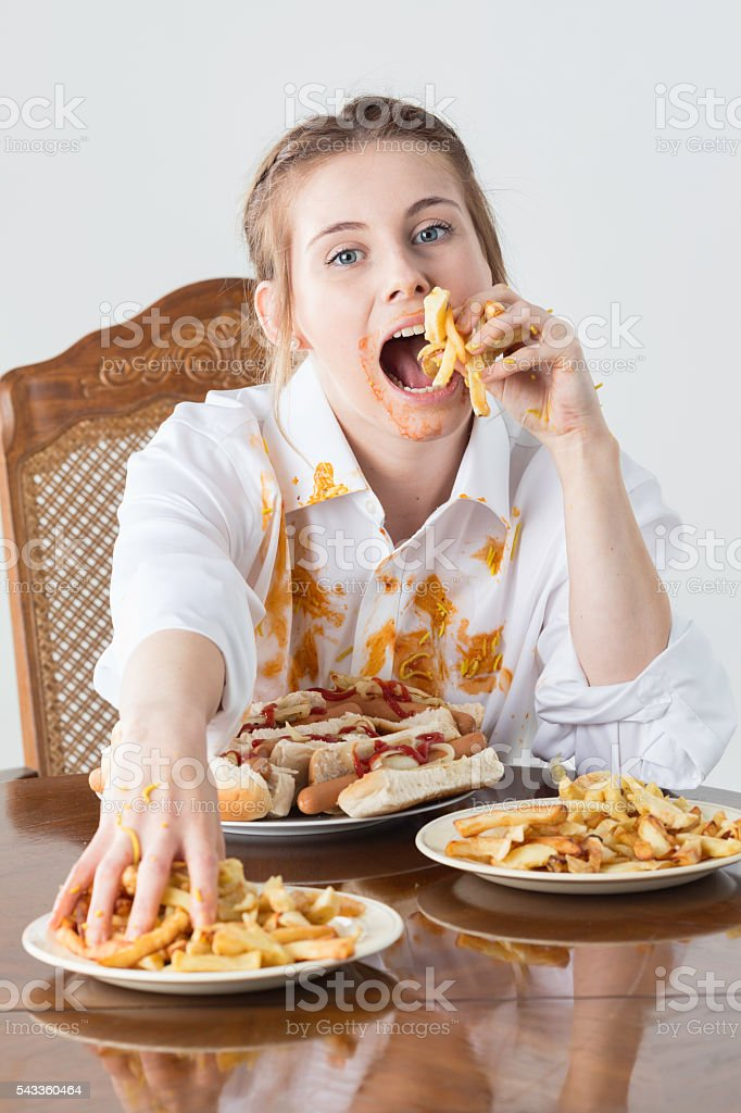 Messy Eater With Hotdogs And Fries stock photo