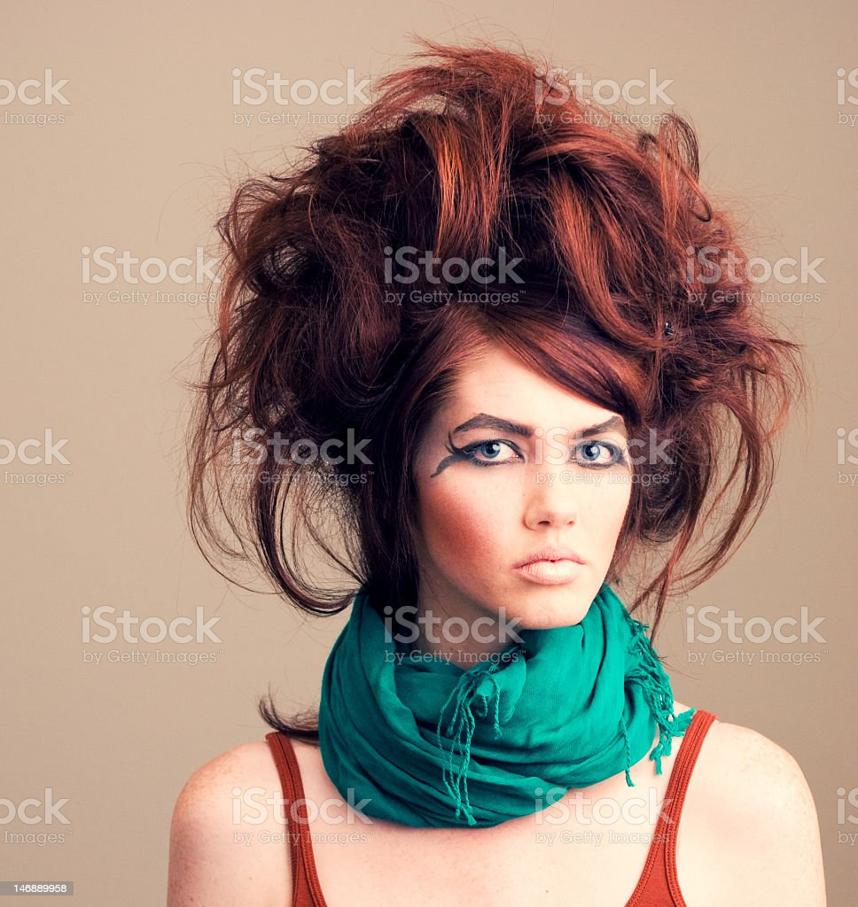 Messy high rise hair and crazy eye makeup on a model stock photo