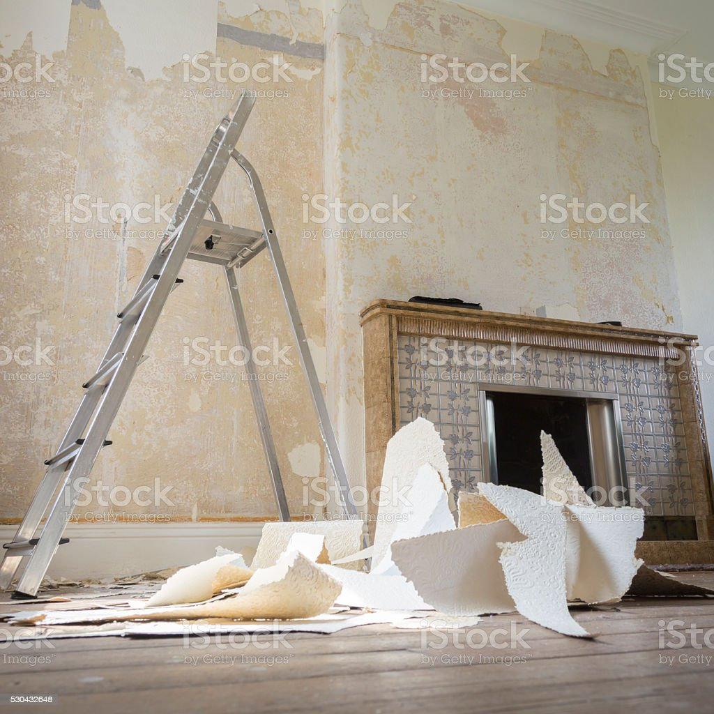 Messy home improvement stripping wallpaper around fireplace stock photo