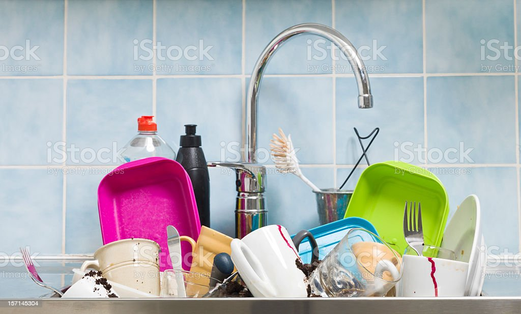 Messy kitchen with dishes in the sink stock photo