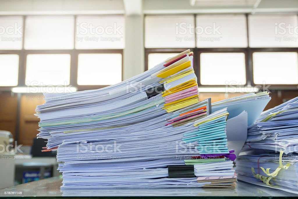 Messy office desk, Pile of unfinished paperworks stock photo