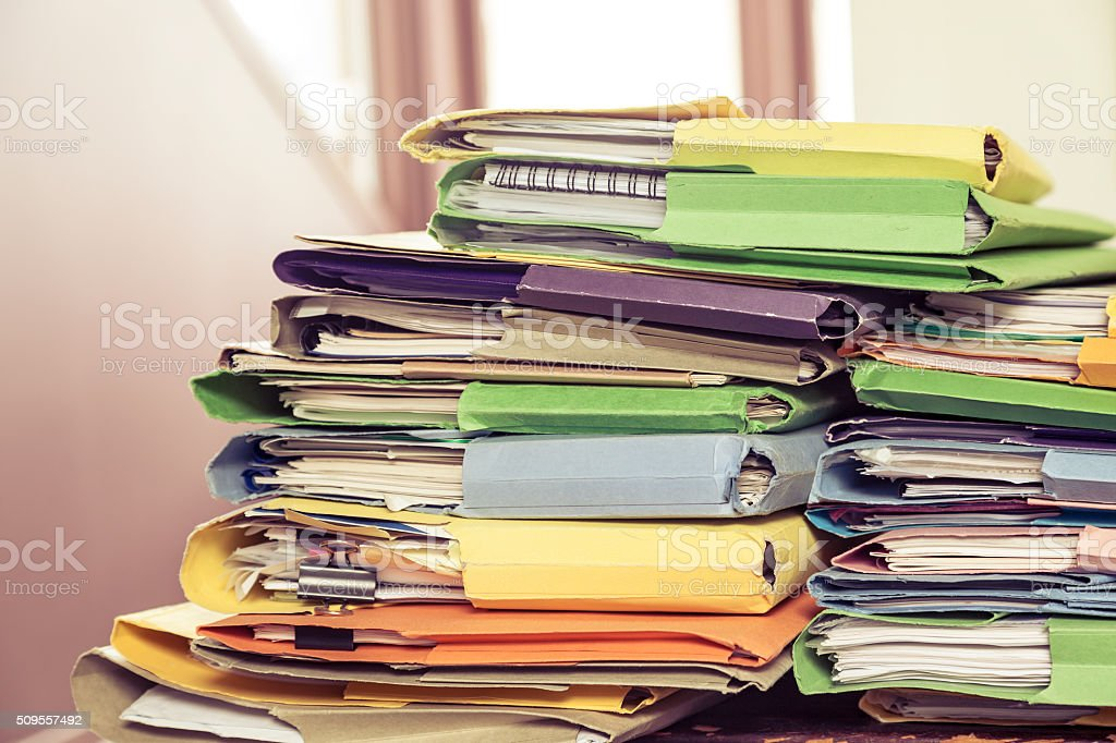 Messy piles of home office paperwork in coloured folders stock photo
