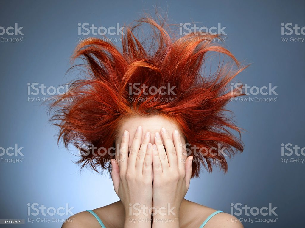 Messy red hair on woman covering her face with her hands stock photo