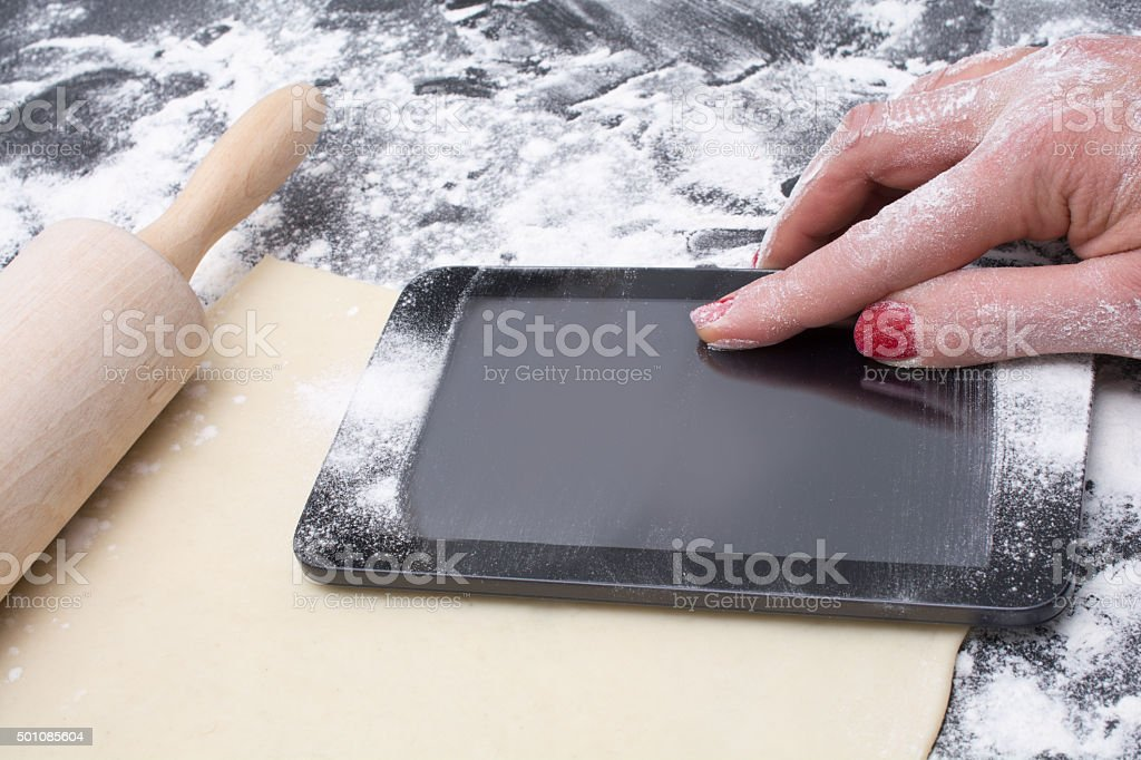 messy tablet with flour on black counter rolled out dough stock photo