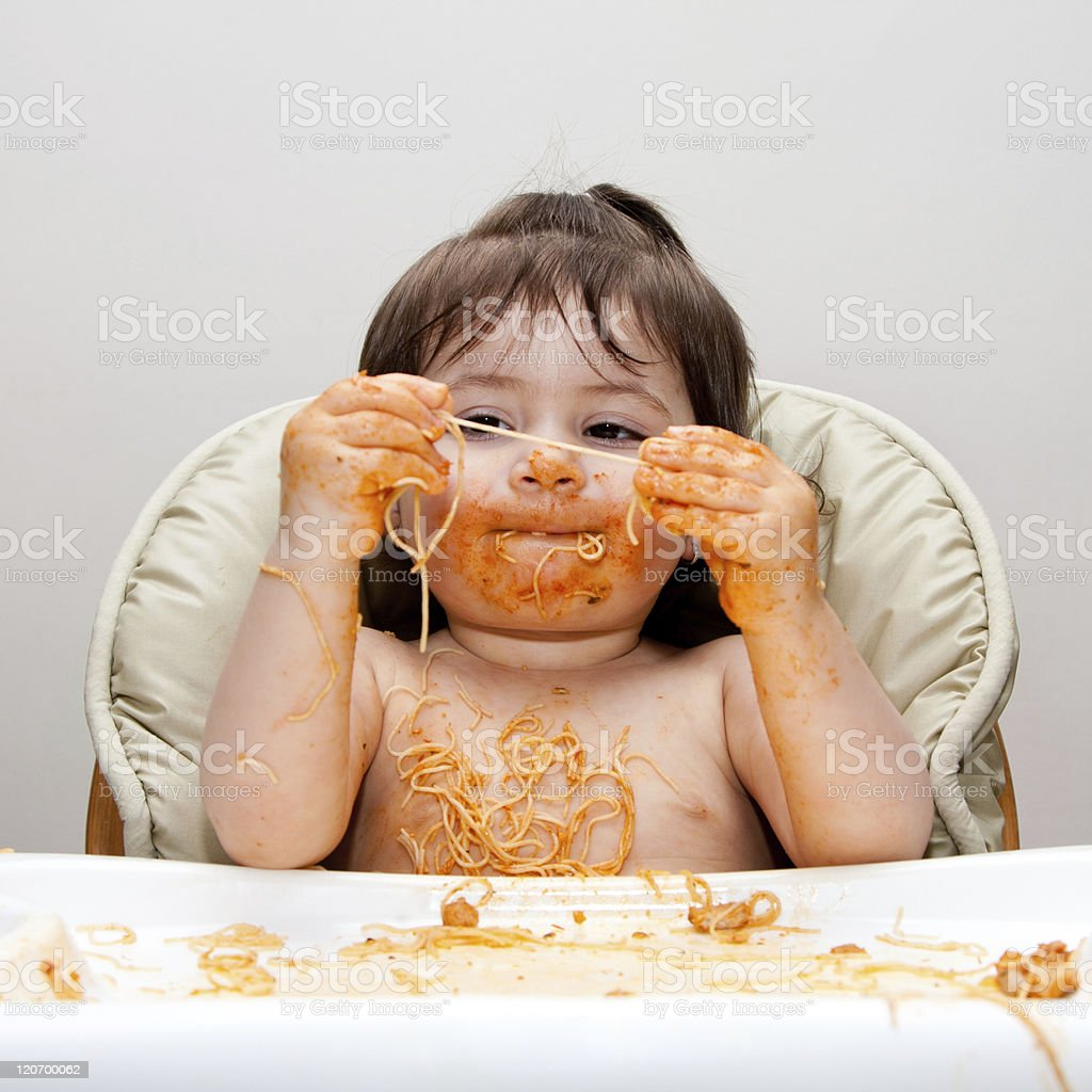 Messy Toddler sitting on high chair playing with food royalty-free stock photo