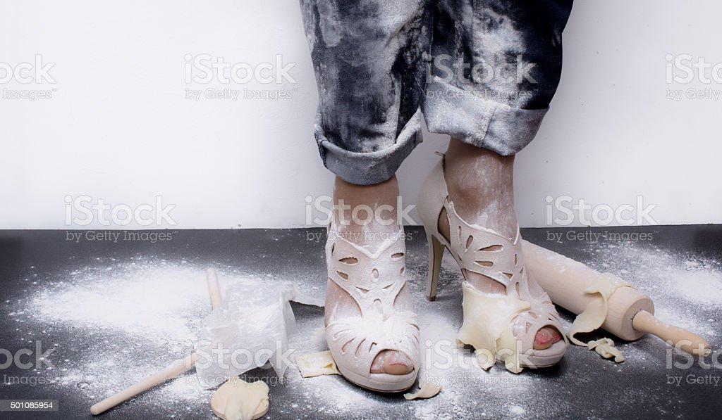 messy woman covered in flour heels and dough flaps stock photo