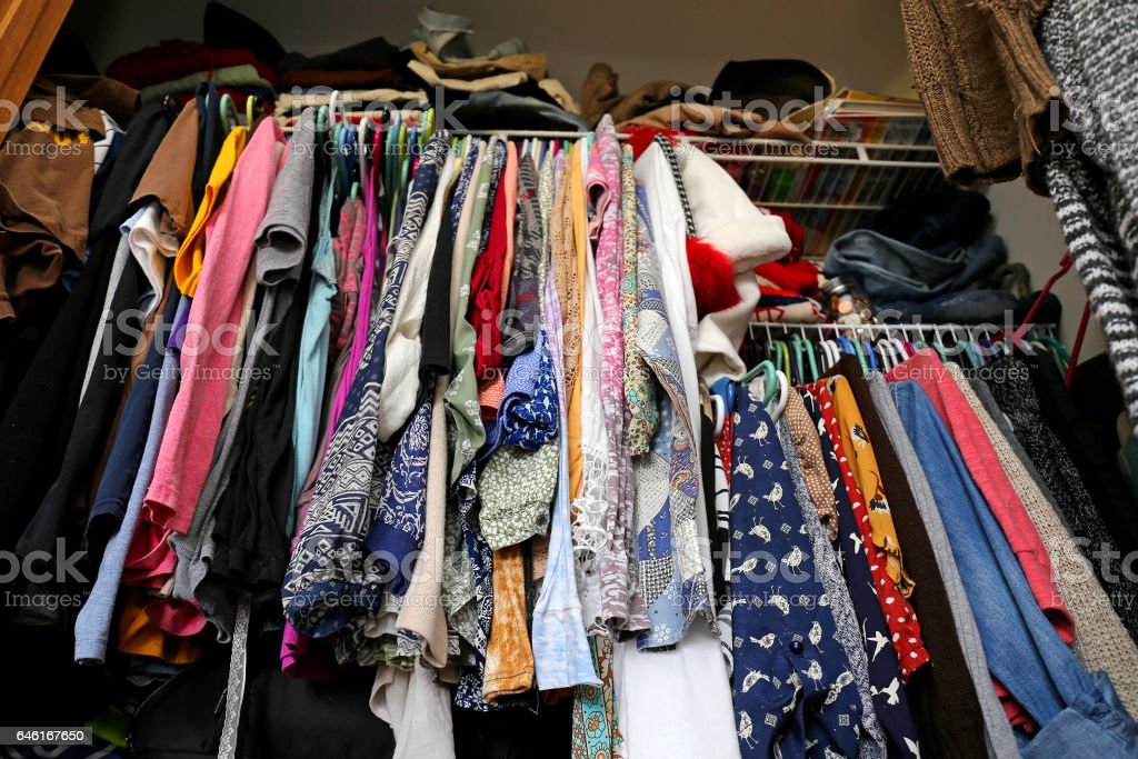 Messy Women's Closet Filled with Colorful Clothes stock photo