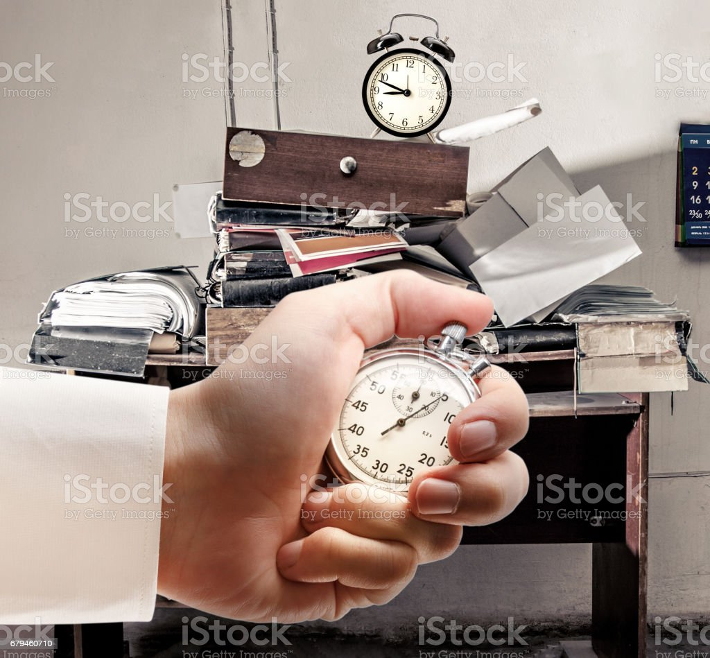 Messy workplace, alarm clock and stopwatch in male hand